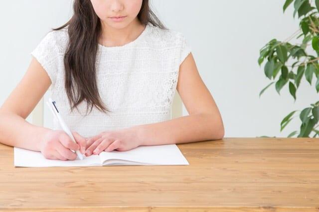 ノートにメモをとる女性