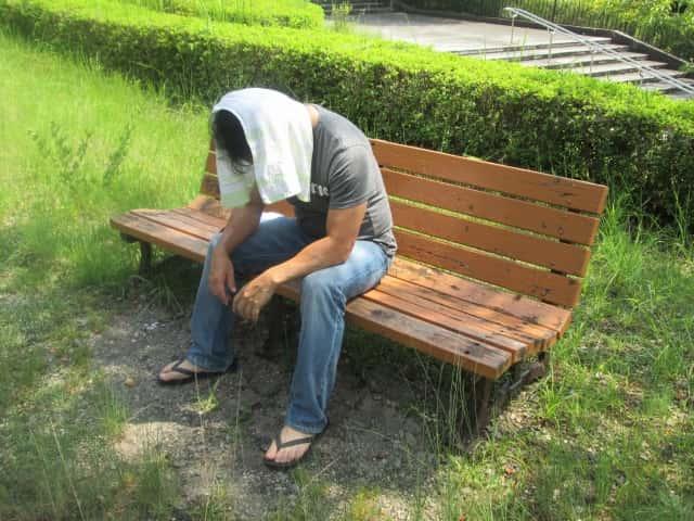 頭にタオルを載せてベンチで休む男性