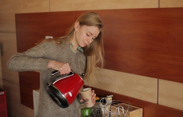 ポットからカップに飲み物を注ぐ女性