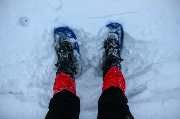 雪の上に立つ足カバーを付けた人の脚