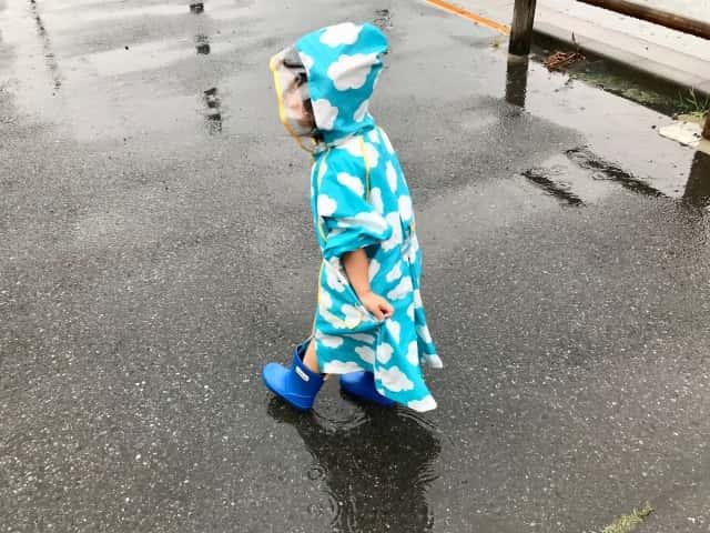 雨の中、空色のレインコートを着る子供