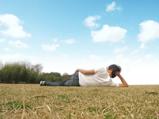 青空の元、野外で昼寝する男性
