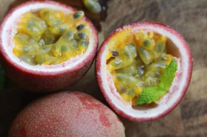 パッションフルーツを切ると、中から鮮やかな黄色の果肉があらわれる