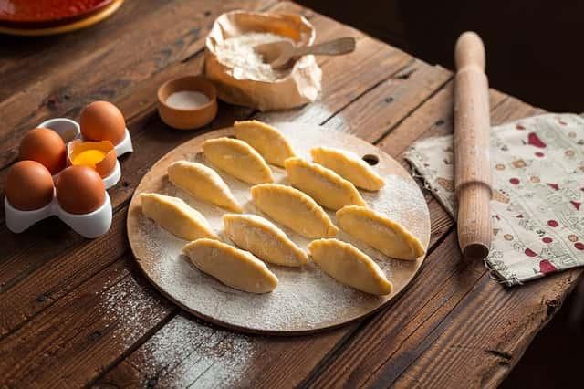 テーブルの上に卵や小麦粉、これから焼き上げるパイのお菓子が乗っている
