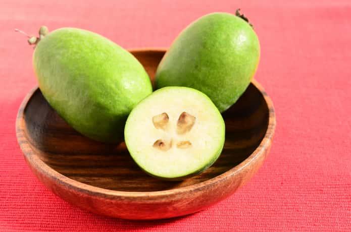 赤いテーブルクロスの上に、木の器に入った緑のフェイジョアが3つ