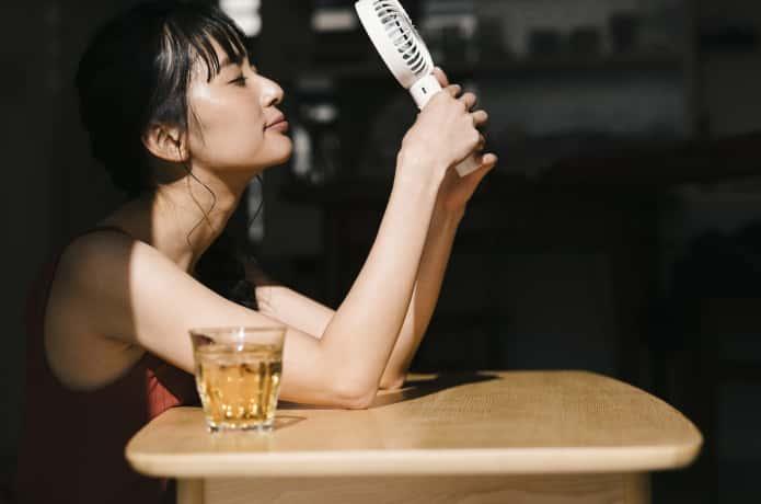 携帯扇風機を使用する女性