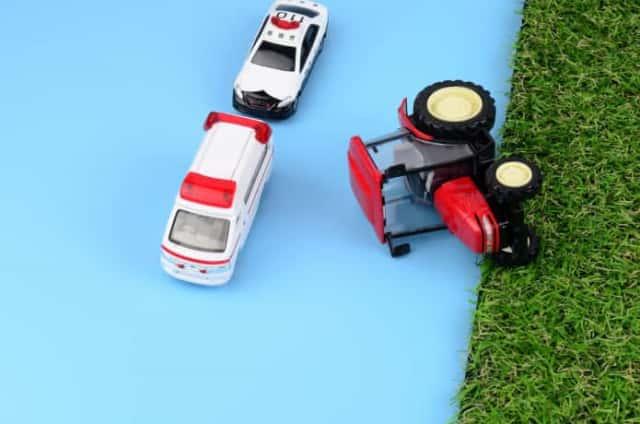 横転したトラクターと緊急車両