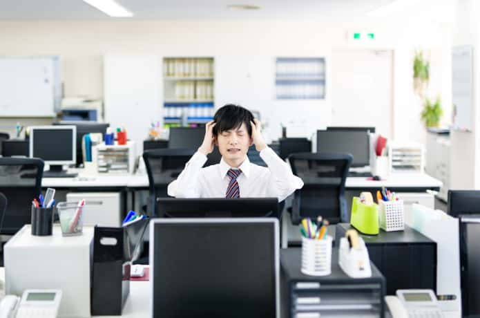 オフィスの席で困っている男性