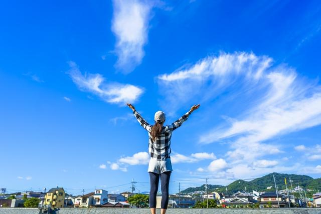 大空に手を広げる女性