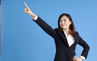 指をさすスーツ姿の女性
