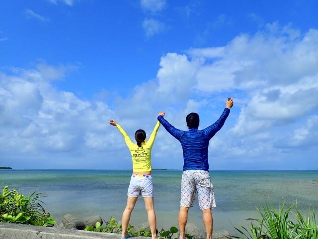 海岸で手を挙げる男女