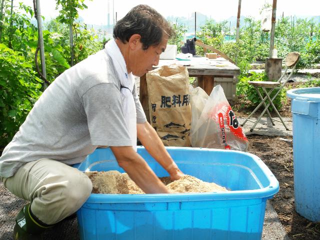 バケツの中で米ぬかと材料を混ぜる