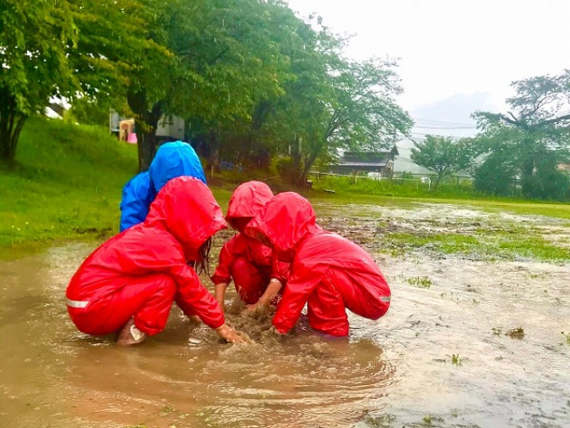 大きな水たまりで遊ぶ子どもたち
