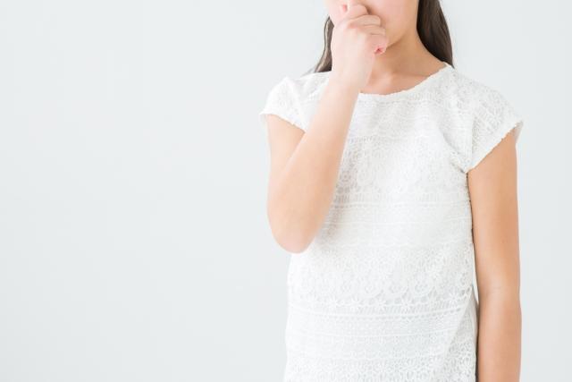 鼻をつまむ白い服の女性