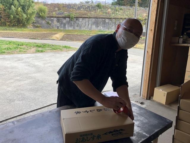 ダンボールを梱包する平山さん